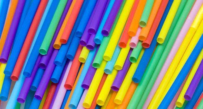 Brightly colored straws thrown around on a table. Some of them are showing the lower side of the tube, with only a few of the flexible heads visible. The colors range from blue to red tones.(flickr/Horia Varlan)