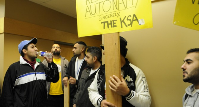 Controversial former Kwantlen Student Association executive Aaron Takhar (far left) stages a protest in support of the 12 recently-impeached board members, on Kwantlen's Surrey campus, Dec. 5. (Matt DiMera/The Runner)
