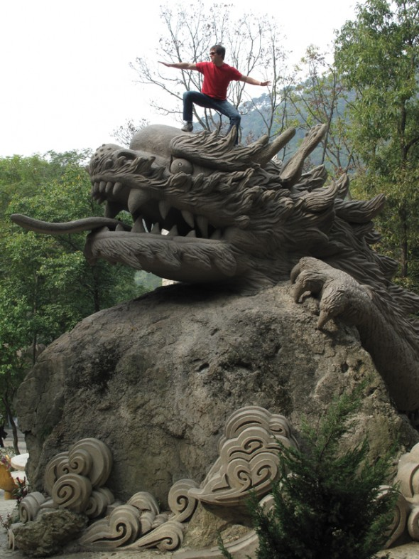 Justin Lukach stands on a stone dragon in North Korea. (Photo courtesy Justin Lukach)
