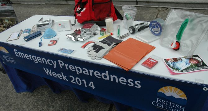 The BC Liberal party displays the typical contents of a disaster emergency kit, during a demonstration in 2014. (flickr/Province of British Columbia)